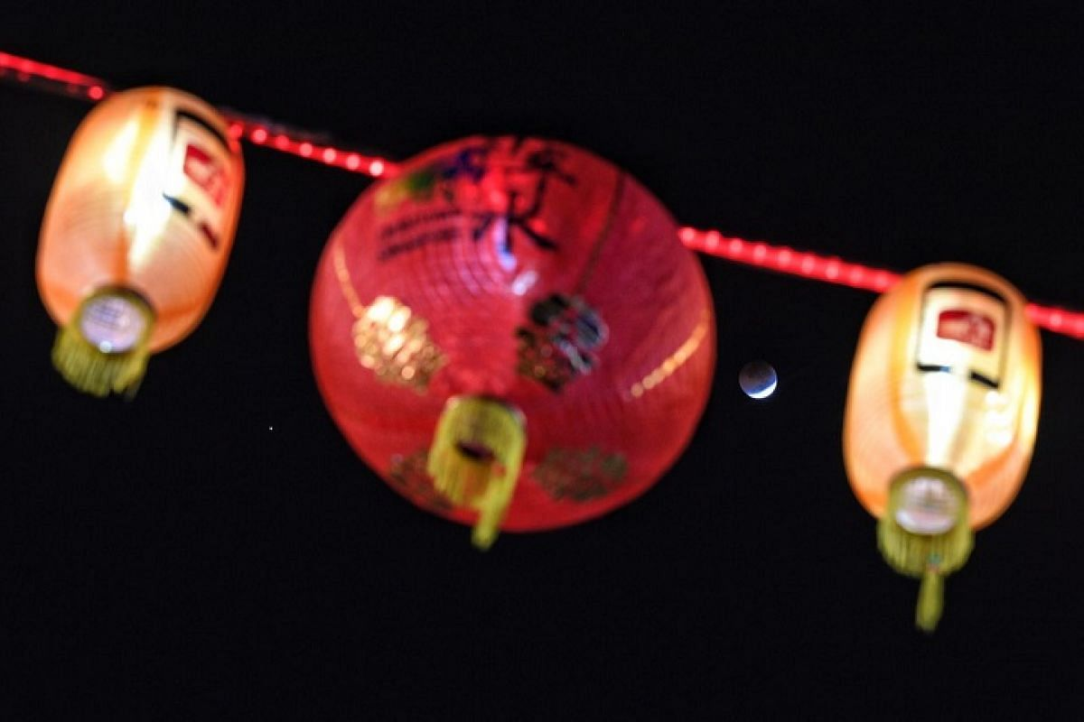 Framed by Chinese lanterns, the moon is seen minutes before the beginning of a total lunar eclipse occurring at 3.30am, in Singapore, on 28 July, 2018.