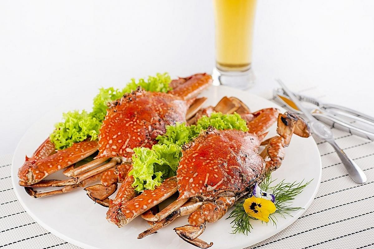 The Baked Flower Crab With Rock Salt (right) has sweet, firm meat enhanced by salt and pepper on the shells and the Crystal Chicken (left) is tender and juicy.