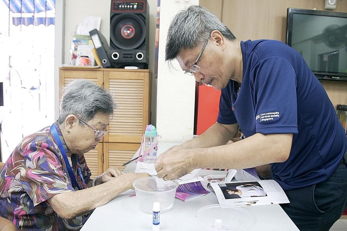 Sales manager Eric Tan volunteers at a seniors activity centre at Block 35 Circuit Road every Saturday for at least four hours. Administrative assistant Deborah Ong and Ms Judith Teo, one of the programme's beneficiaries, learning aboutroad signs and