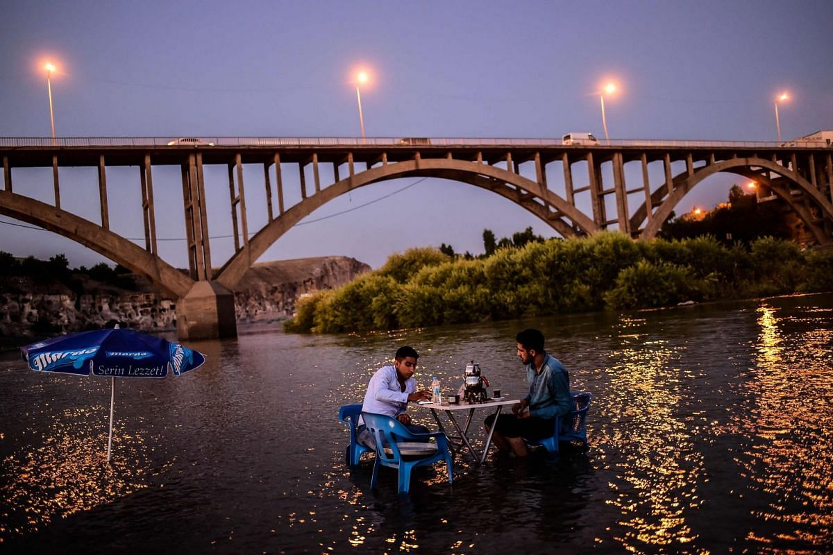 Two men sit at a table placed in the waters of the Tigris River that runs through the 12,000-year-old Hasankeyf settlement  which will soon be significantly submerged by the waters of the nearby Ilisu dam in southeastern Turkey, on July 29, 2018. PHO
