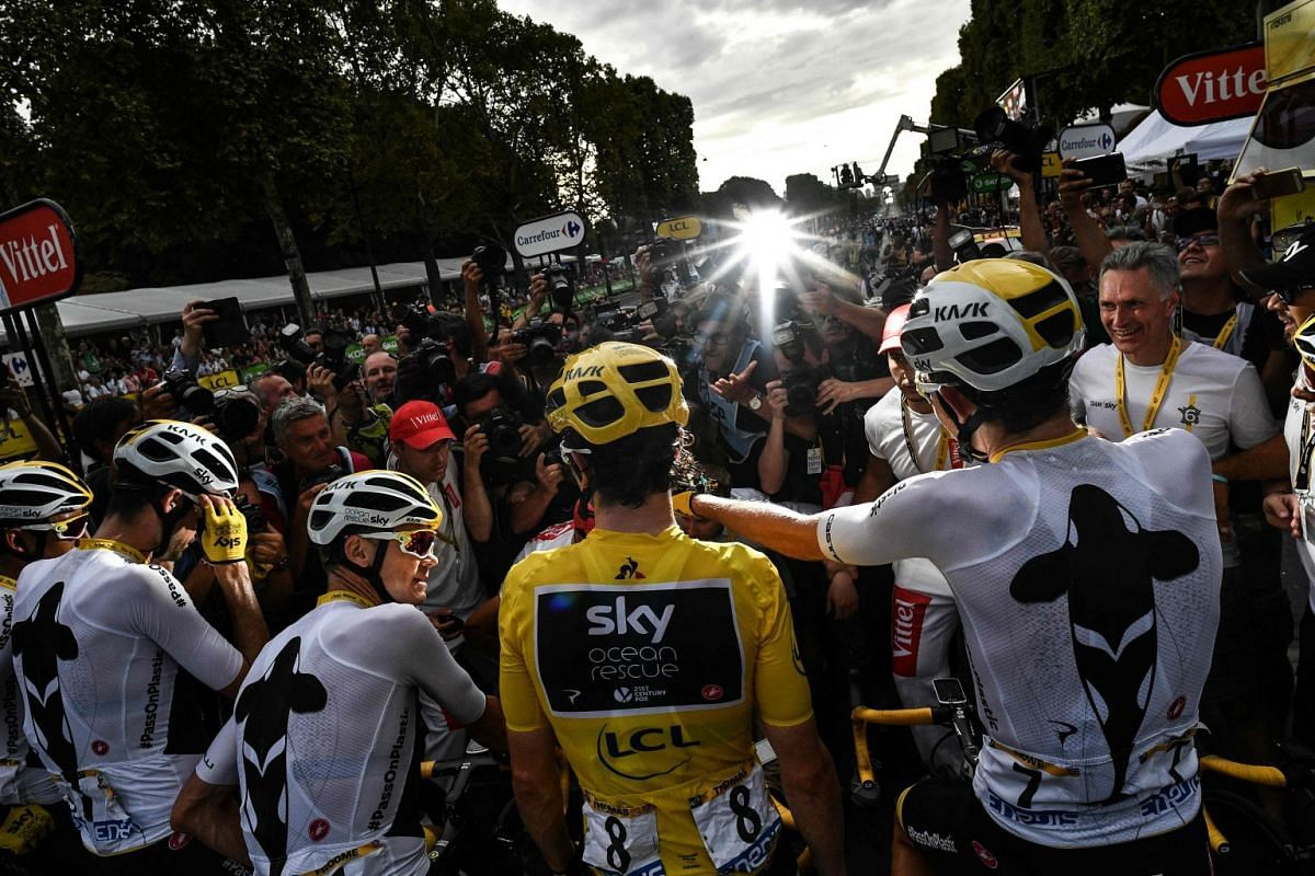 Tour de France winner Great Britain's Geraint Thomas (C) wearing the overall leader's yellow jersey poses with his team for photographers after the 21st and last stage of the 105th edition of the Tour de France cycling race between Houilles and Paris