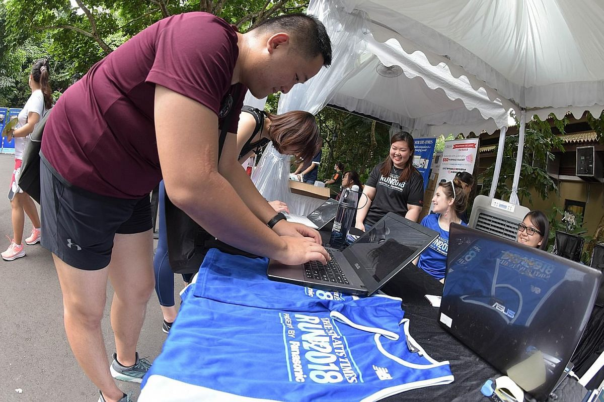 Visitors to The Straits Times Concert in the Gardens signing up yesterday for the ST Run that will be held on Sept 23. They received exclusive ST Run 2018 premiums - a cotton tote bag, a towel and a special water bottle with a misting feature. Childr