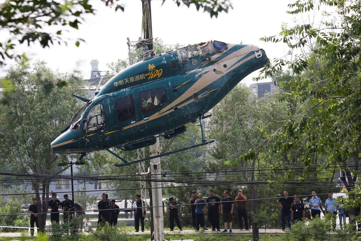 A crane lifts a helicopter after it crashed in Beijing, China, July 30, 2018. PHOTO: REUTERS