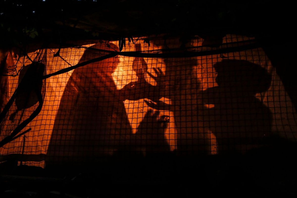 A Palestinian woman uses a gas lamp during a power cut in an impoverished area of the Khan Younis refugee camp, southern Gaza Strip on July 29, 2018. PHOTO: AFP