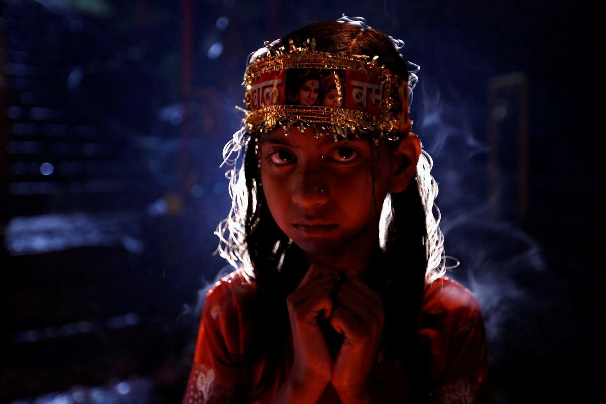 """A girl stands near the burning lamps to keep herself warm as she takes part in the """"Bol Bom"""" (Say Shiva) pilgrimage in Kathmandu, Nepal, July 30, 2018. PHOTO: REUTERS"""
