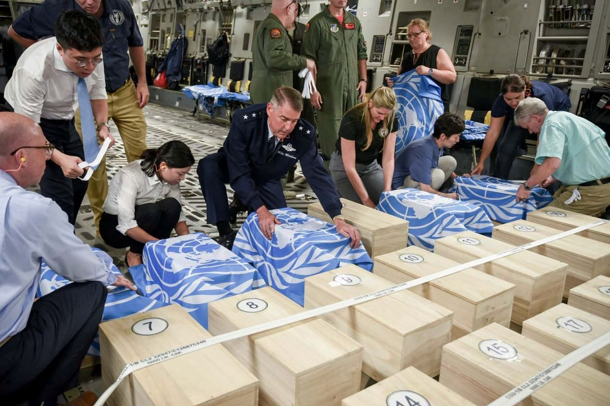 A photo released on July 27, 2018 shows crew and officials from the United Nations Command and U.S. Defense POW/MIA Accounting Agency (DPAA) securing UNC flags over transit cases of remains thought to be of U.S. soldiers killed in the 1950-53 Korean