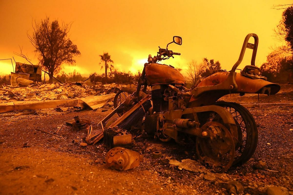 A motorcycle sitting next to a home that was destroyed by the Carr Fire, in which a Redding firefighter and bulldozer operator were killed.