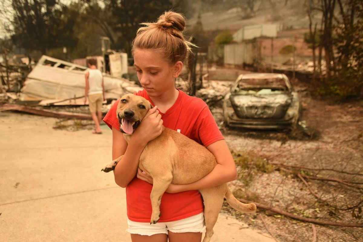 Kambryn Brilz, 12, holds her dog Zoe in front of the remains of her burnt home during the Carr Fire in Redding, California, on July 27, 2018.