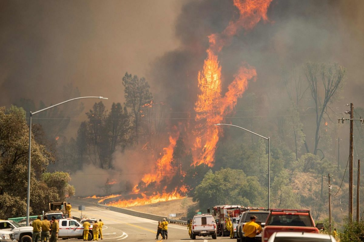 Flames tower above firefighters during the Carr Fire near Whiskeytown of California, on July 27, 2018.