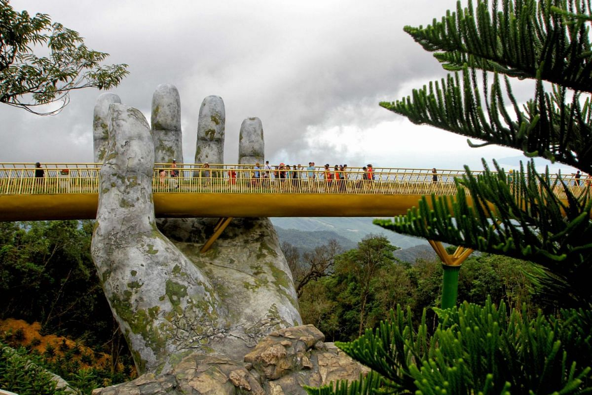 """Visitors walk along the 150-meter long Cau Vang """"Golden Bridge"""" in the Ba Na Hills near Danang, July 31, 2018. Nestled in the forested hills of central Vietnam two giant concrete hands emerge from the trees, holding up a glimmering golden bridge. PHO"""