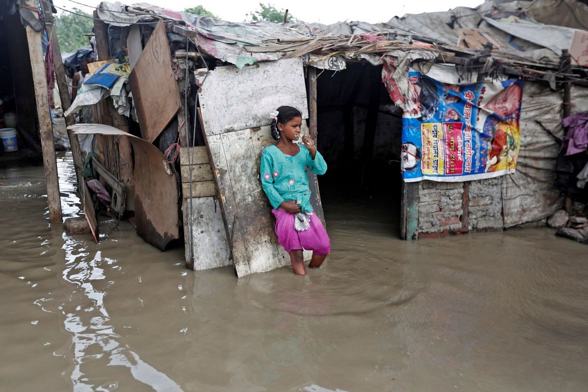 A girl brushes her teeth as she stands outside her submerged shanty at a slum area after a rise in the waters of the river Yamuna in New Delhi, India, July 31, 2018. PHOTO: REUTERS