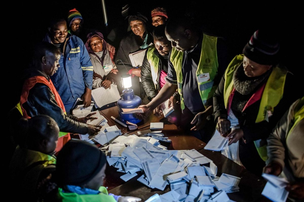 Observers check the tally of votes at a polling station for the general election in the suburb of Mbare of Zimbabwe's capital Harare on July 30, 2018. PHOTO: AFP