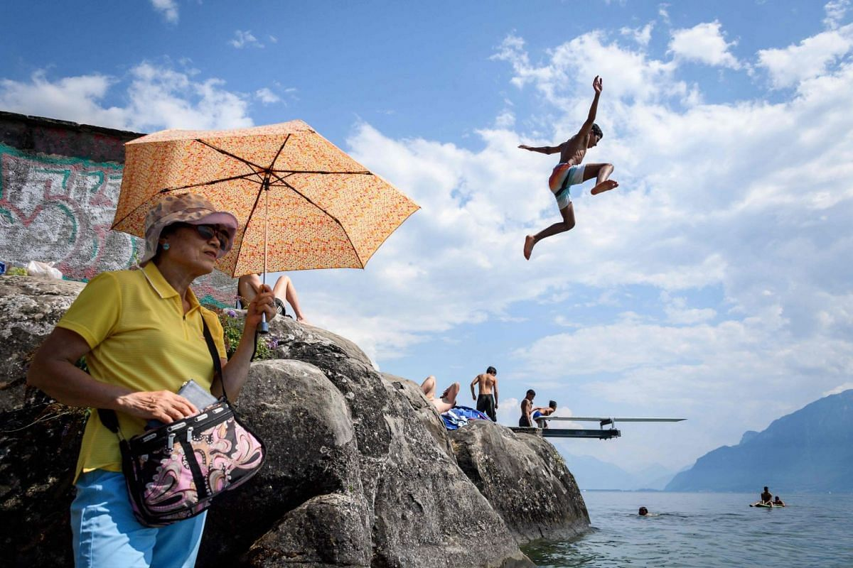 A boy jumps into Geneva Lake in Saint Saphorin, western Switzerland, above a tourist protecting herself from the sun with an umbrella as a heatwave is sweeping across northern Europe on July 31, 2018. PHOTO: AFP