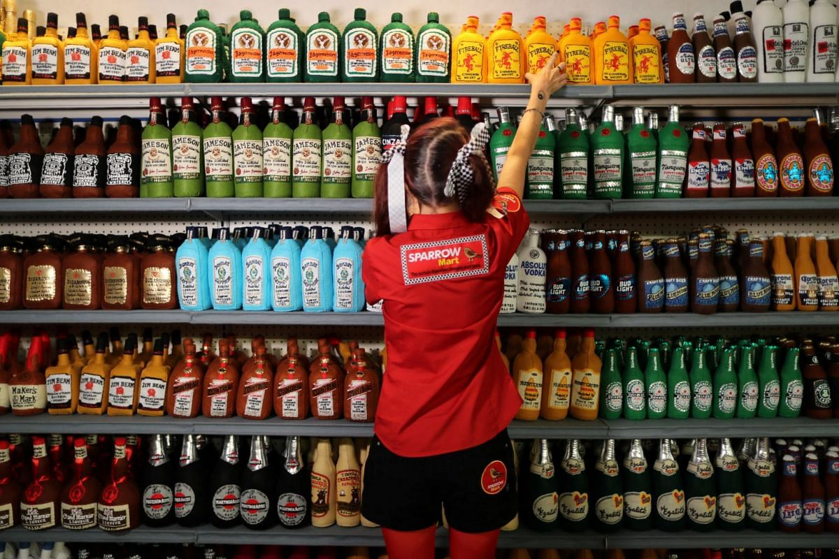 British artist Lucy Sparrow, 32, adjusts bottles of alcohol on shelves in her art installation supermarket in which everything is made of felt, in Los Angeles, California, U.S. July 31, 2018. PHOTO: REUTERS