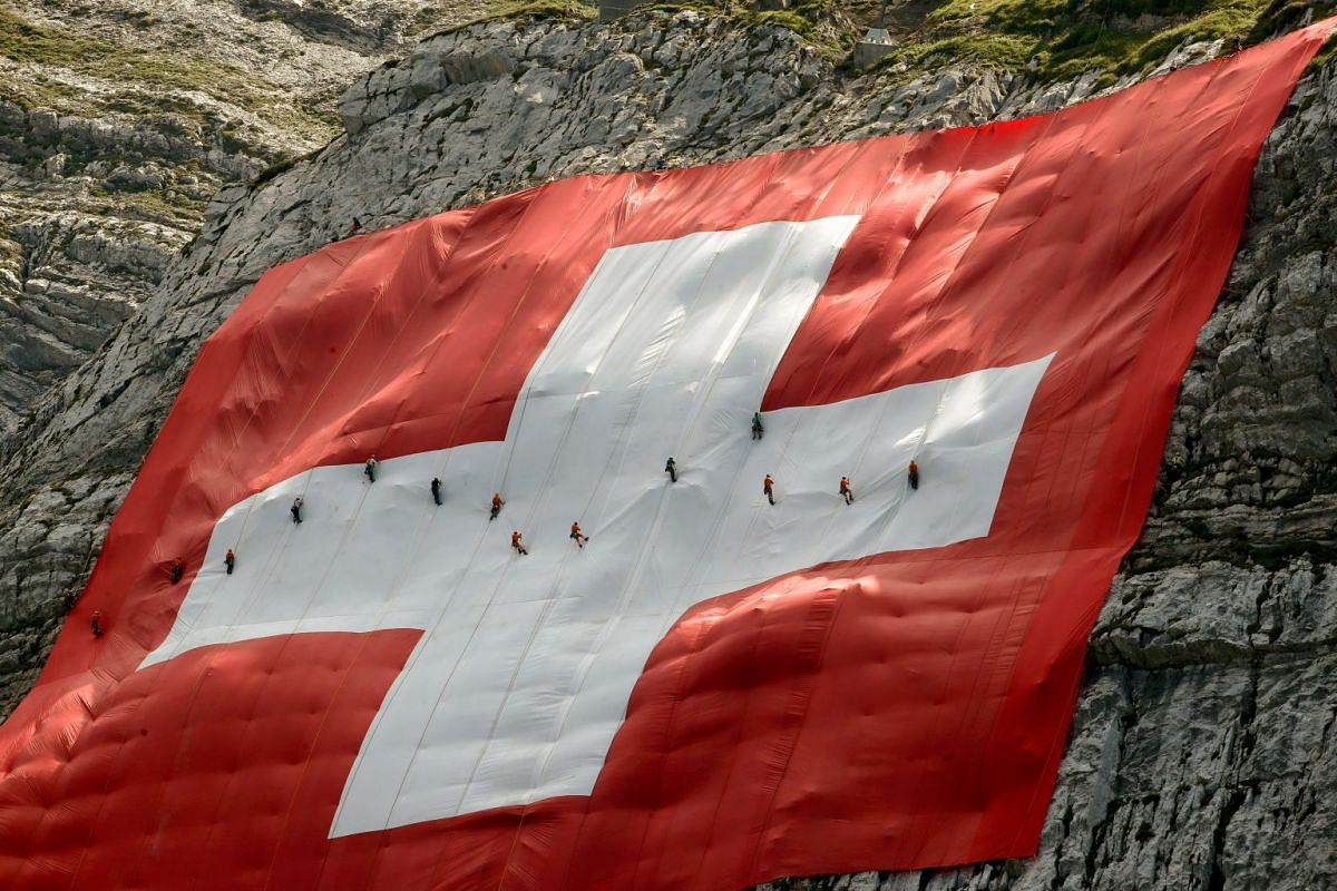 Climbers are seen on a huge 80x80 metres (262x262 feet) Swiss national flag after fixing it on the western face of the north-eastern Swiss landmark Mount Saentis, Switzerland July 31, 2018. PHOTO: REUTERS