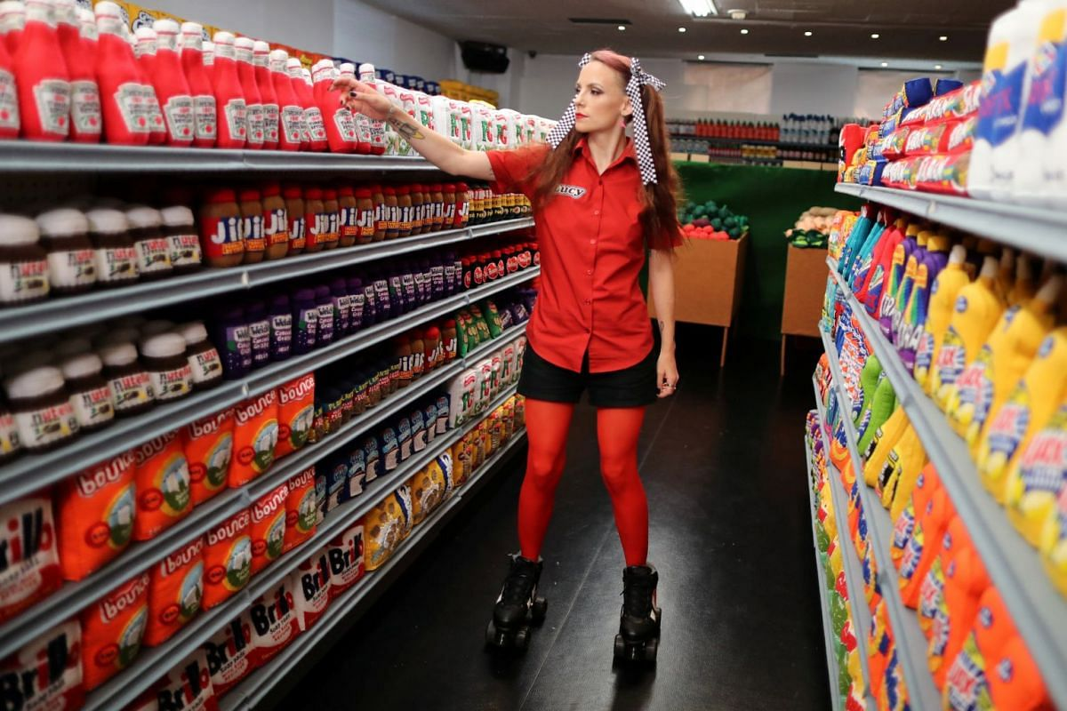 British artist Lucy Sparrow, 32, adjusts bottles of ketchup on shelves in her art installation supermarket in which everything is made of felt, in Los Angeles, on July 31, 2018.