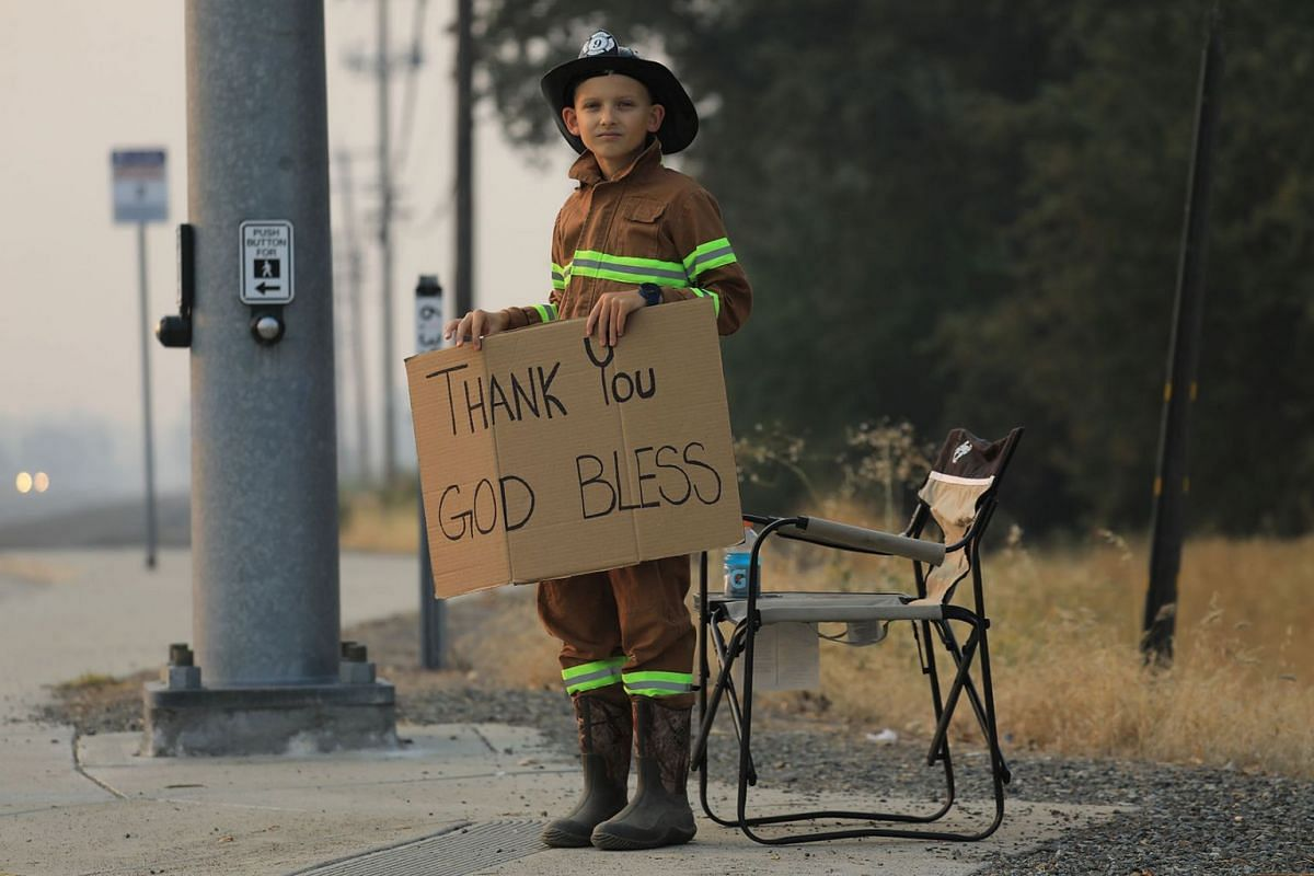 Kenny Garrison, 8, dressed as a firefighter on a street corner near his home in Redding, Calif., Aug. 1, 2018. A wildfire in the area, named the Carr Fire, has killed at least six people and displaced tens of thousands thus far. PHOTO: THE NEW YORK T