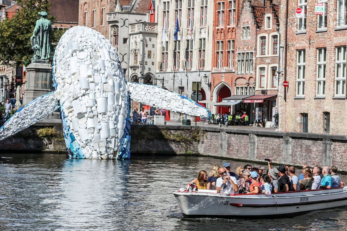 A boat of tourists sails past a 12-metre installation depicting a whale, made up of five tons of plastic waste pulled out of the Pacific Ocean, displayed in Bruges, Belgium, 01 August 2018. PHOTO: EPA-EFE