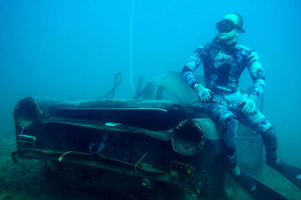 A diver poses for a photograph next to an immersed tank off the coast of the southern Lebanese port city of Sidon on August 1, 2018. PHOTO: AFP