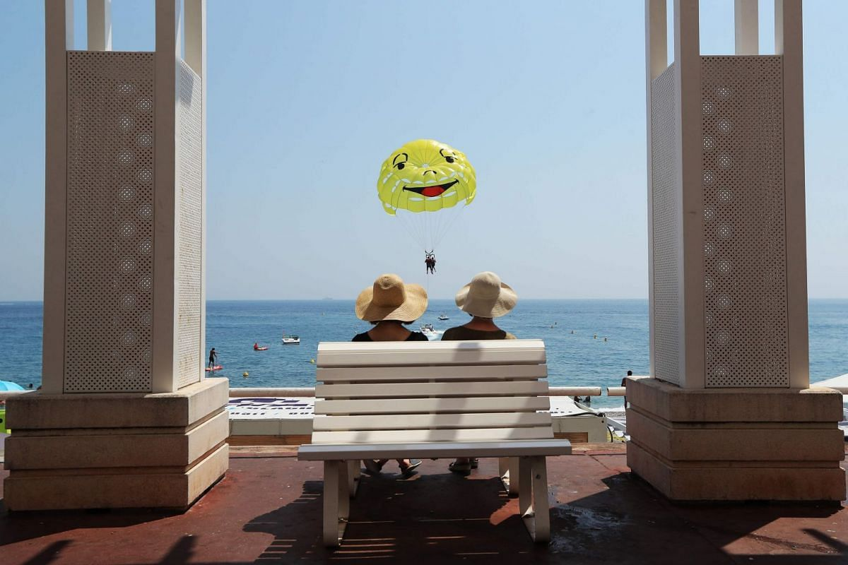 People sit on a bench while people parasail on the beach as a heatwave is sweeping across northern Europe on August 1, 2018 in Nice, on the French Riviera. PHOTO: AFP
