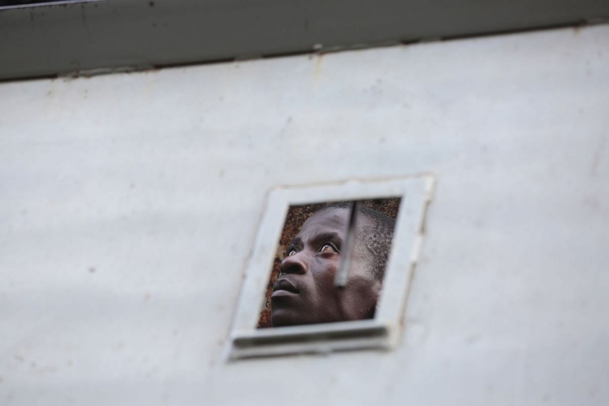 One of the 16 Movement For Democratic Change (MDC) Alliance members, who have been arrested by the Zimbabwe Republic Police (ZRP) at the party's headquarters, looks through a small window of a police truck in Harare, Zimbabwe, August 2, 2018. PHOTO:
