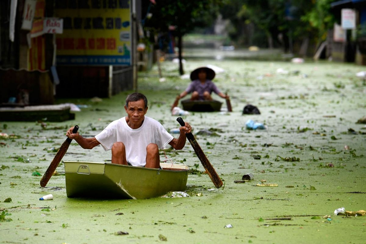 People row in boats through floodwaters in Hanoi's suburban Chuong My district on August 2, 2018. PHOTO: AFP
