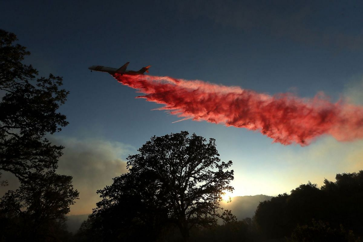 A firefighting aircraft drops fire retardant ahead of the River Fire as it burns through a canyon on August 1, 2018 in Lakeport, California. PHOTO: GETTY IMAGES/AFP