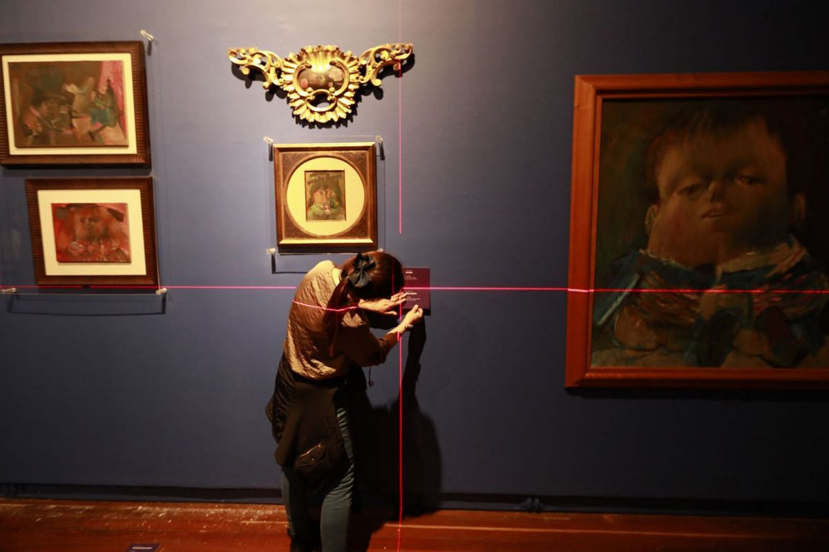 """A woman prepares the exhibition """"Joven Maestro"""" of the early works of Colombian artist Fernando Botero, at the National Museum in Bogota on August 2, 2018. PHOTO: AFP"""