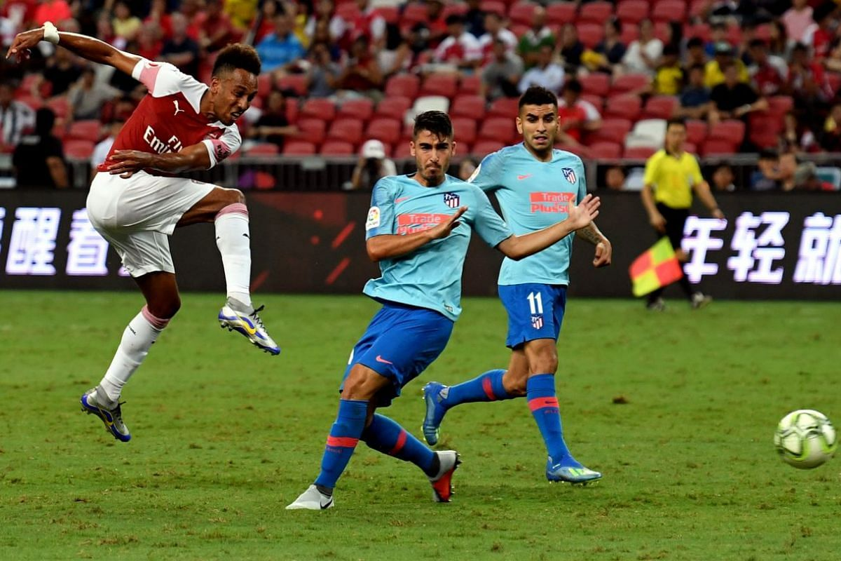 Arsenal's Gabonese striker Pierre-Emerick Aubameyang shooting at goal as an Atletico Madrid defender tries to close him down during their International Champions Cup match in Singapore last week.