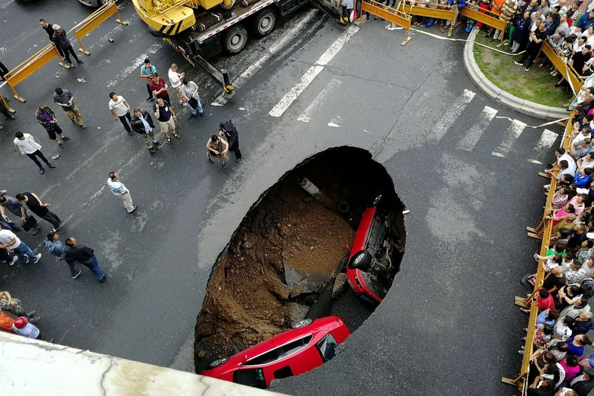 People gather near the scene where two vehicles have fallen into a sinkhole on a street in Harbin, Heilongjiang province, China August 4, 2018.