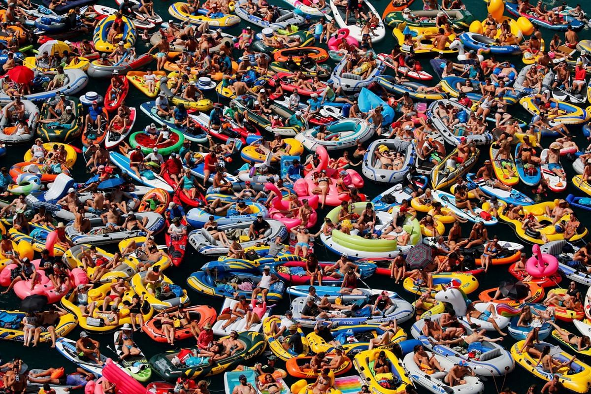 People on inflatable boats enjoy the weather on the Lake Lucerne in Sisikon, Switzerland, August 5, 2018.