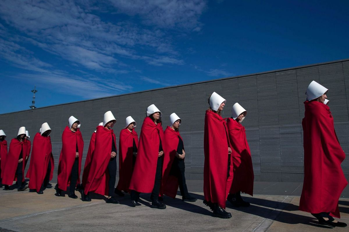"""Activists in favour of the legalization of abortion disguised as characters from Canadian author Margaret Atwood's feminist dystopian novel """"The Handmaid's Tale"""", perform at the """"Parque de la Memoria"""" (Remembrance Park) in Buenos Aires, on August 5,"""