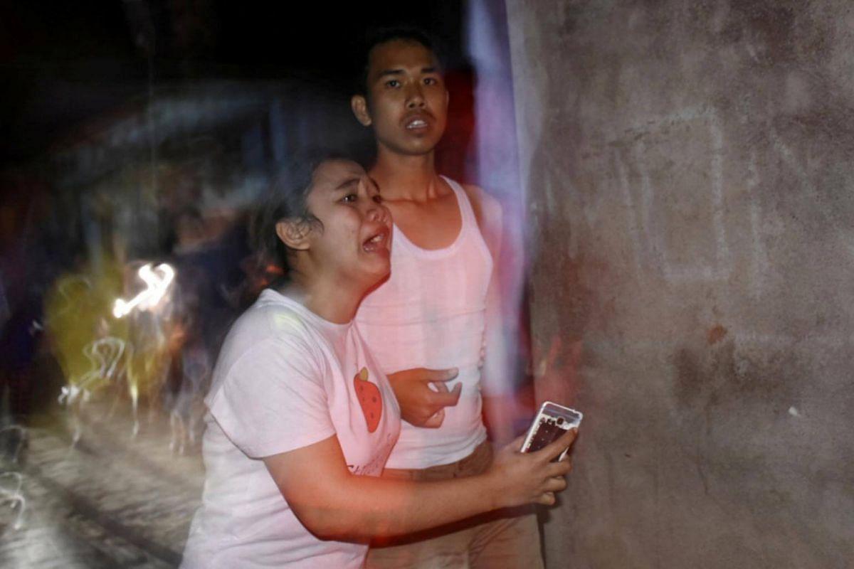 People react following an earthquake in Ampenan district, Mataram, Lombok, on Aug 5, 2018.
