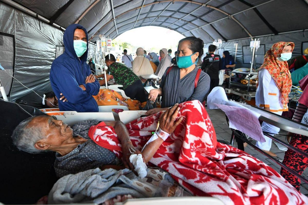 An elderly man rests in a hospital bed at a makeshift ward set up outside the Moh. Ruslan hospital in Mataram, Lombok, on Aug 6, 2018.