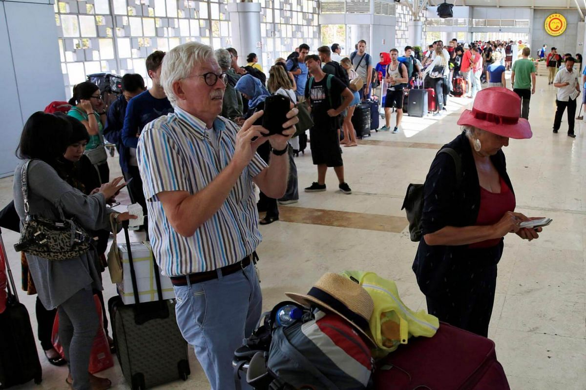 Foreign tourists queue to leave Lombok Island after an earthquake hit, as seen at Lombok International Airport, on Aug 6, 2018.