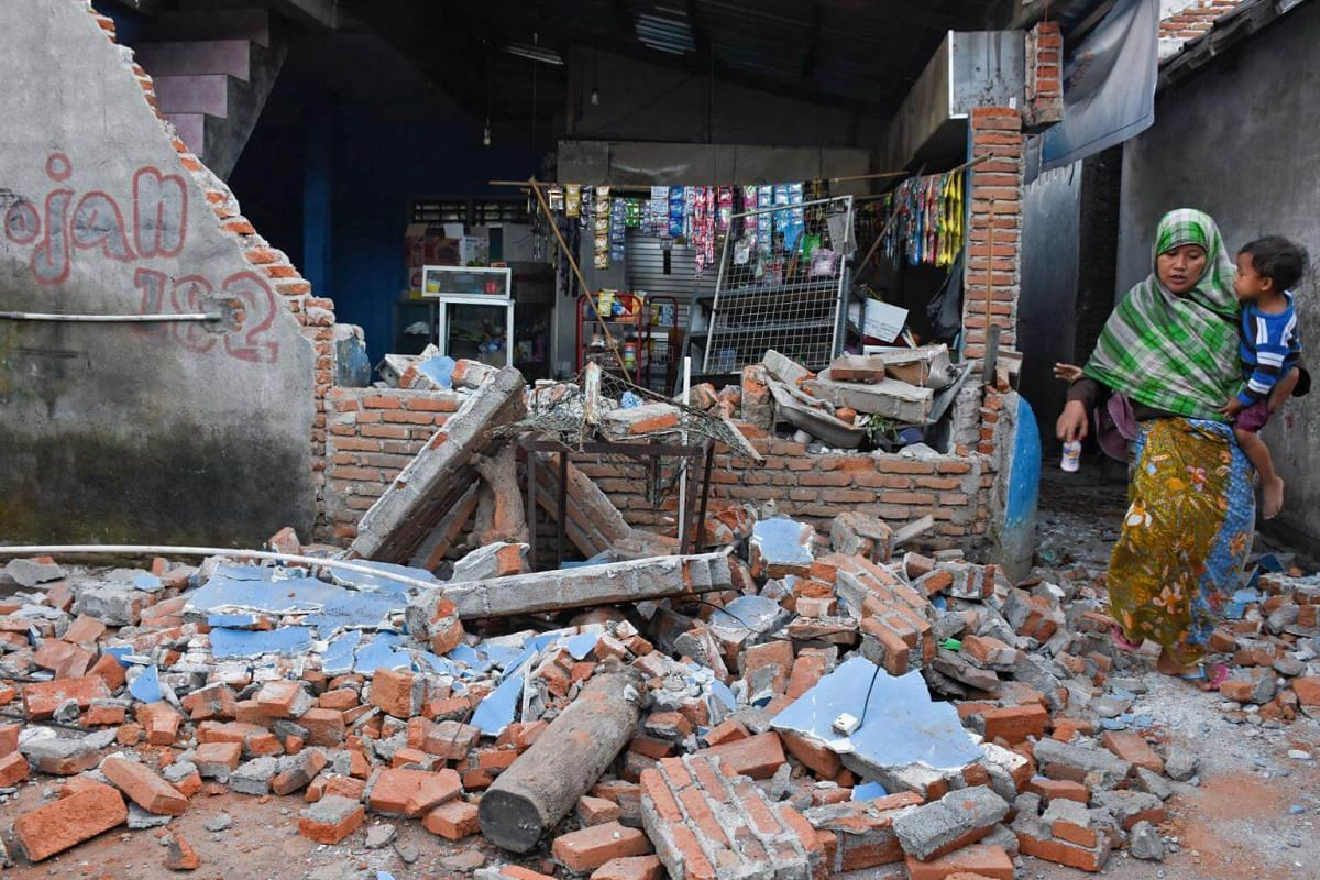 A woman walks past debris from a collapsed wall following a strong earthquake in Lendang Bajur Hamlet, Lombok, on Aug 6, 2018.