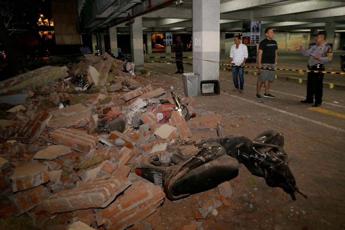 A policeman examines debris that fell and crushed parked motorbikes at a shopping center in Kuta, Bali, on Aug 5, 2018.