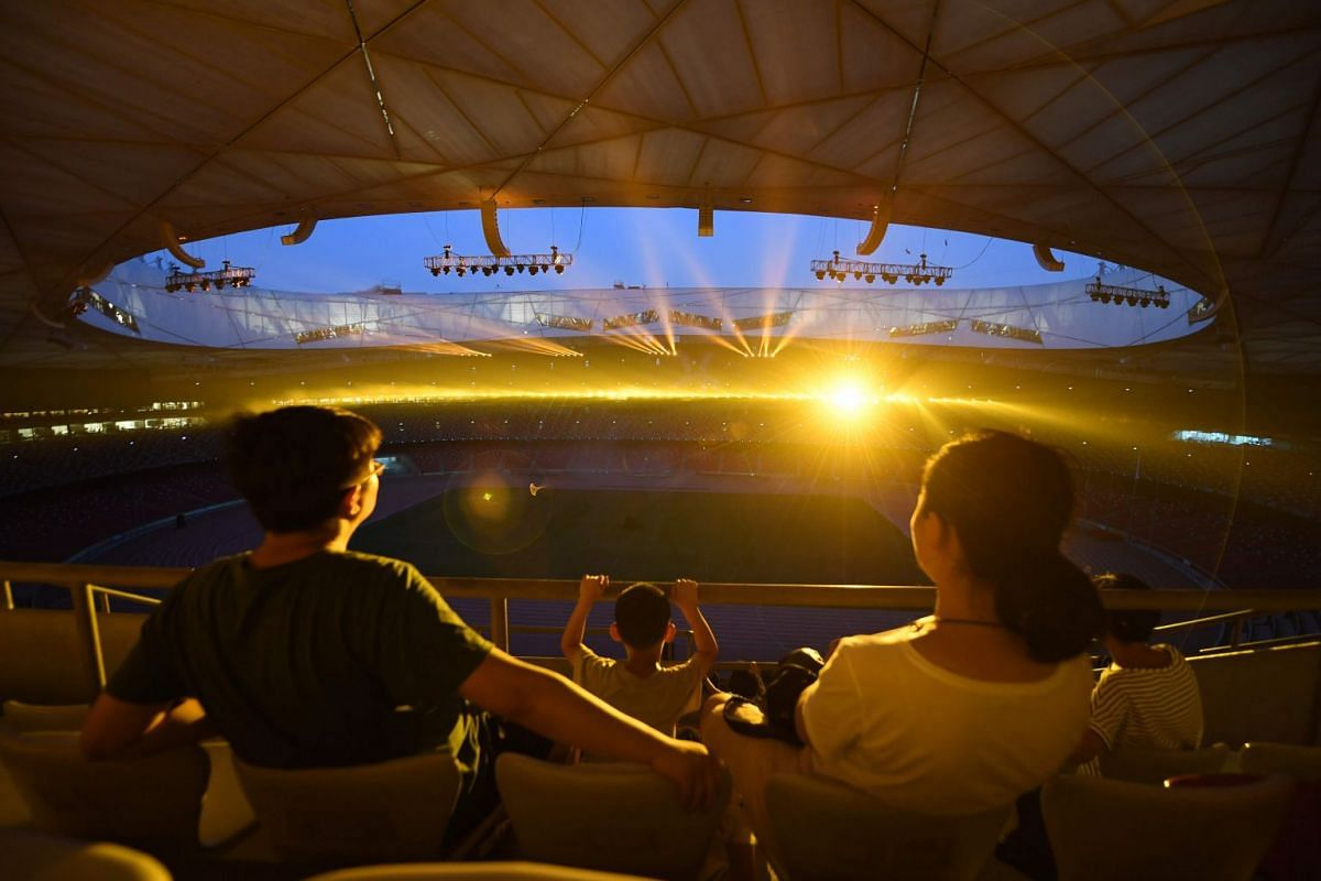 A family watching a light show held to mark the 10th anniversary of the 2008 Beijing Olympic Games, at the National Stadium, known as the Bird's Nest, in Beijing, August 1, 2018.