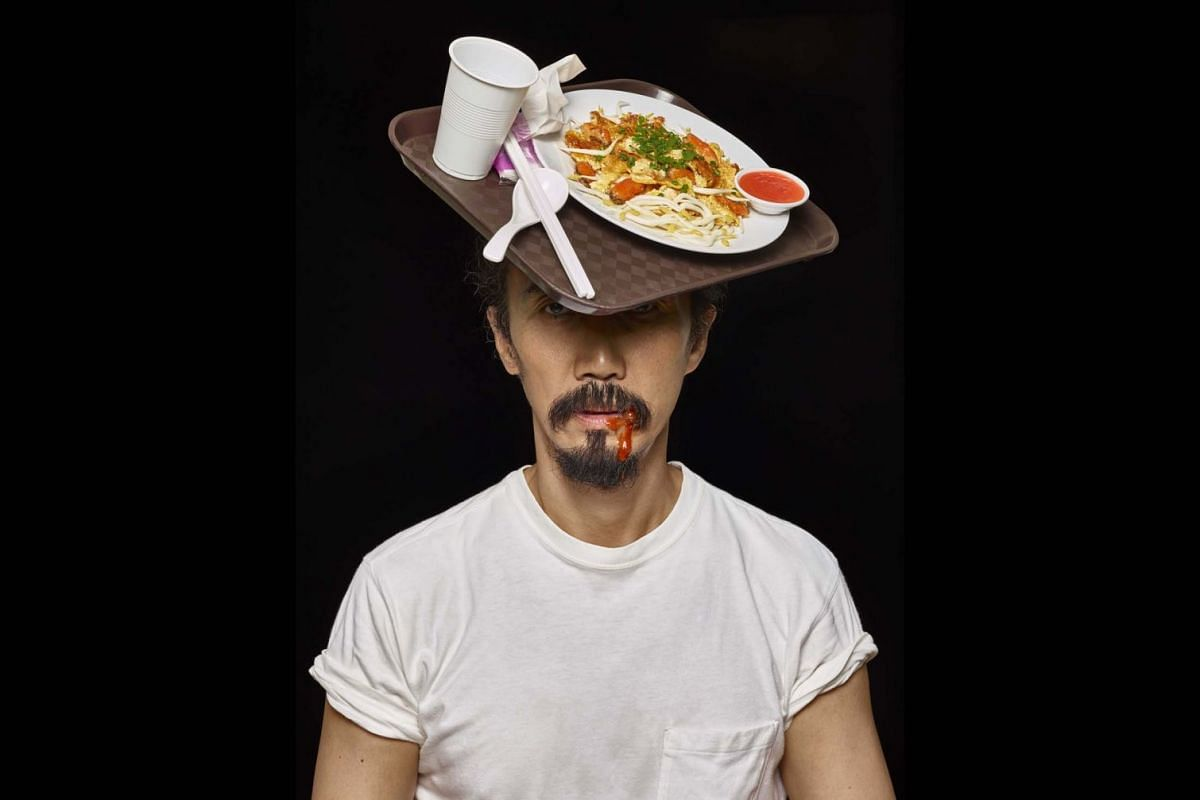 Mr Yang's various costumes include: A tray of completed food on his head to remind people to return their tray after a meal.