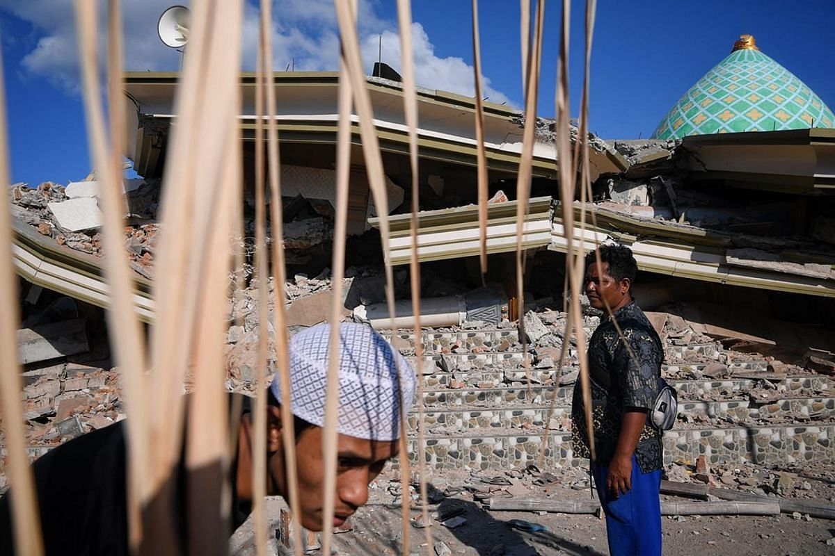 Villagers of Karang Pangsor at the collapsed Jami'ul Jama'ah mosque, where at least five people are still stuck under the rubble.