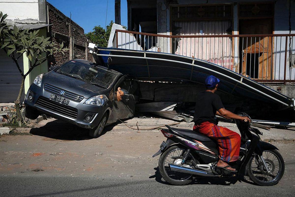 A car stuck under a collapsed shelter near the village of Karang Pangsor, Lombok, on Aug 7, 2018.