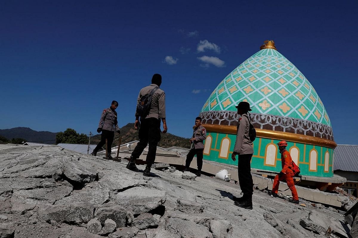 Rescuers and policemen on top of a collapsed mosque as they try to find survivors after an earthquake hit on Sunday in Pemenang, Lombok Island, Indonesia, on Aug 7, 2018.