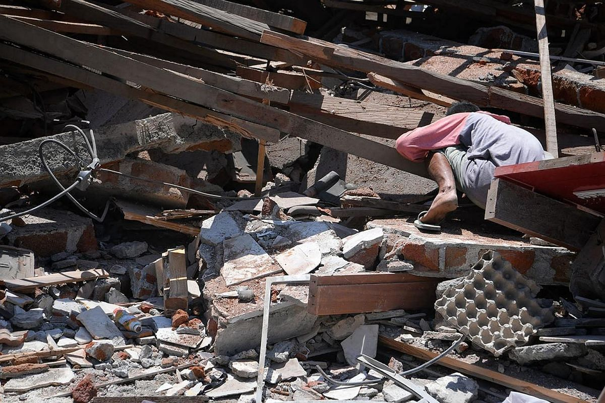 One of several villagers searching for Dea Mukti, 21, who is believed to be trapped under the rubble in the village of Karang Montong Laut on Indonesia's Lombok island, on Aug 7, 2018.