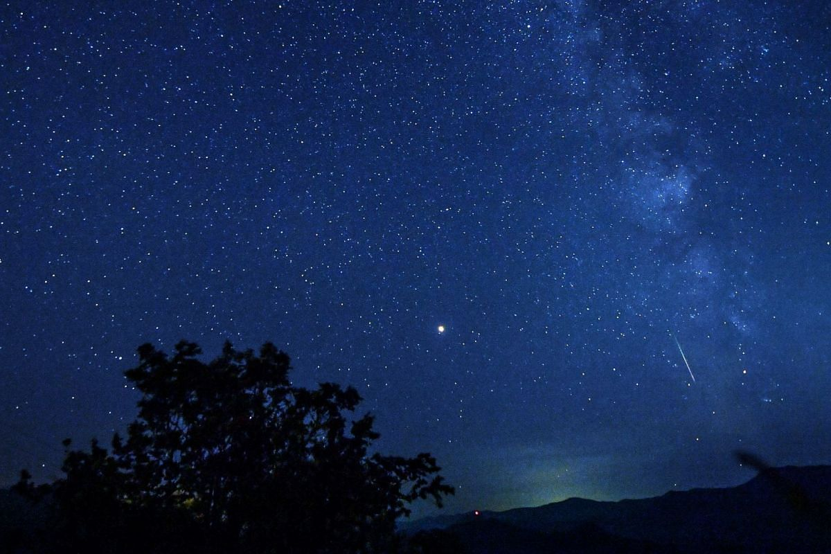 Meteors streak past stars in the night sky over the lake of Kozjak in Macedonia during the Perseid meteor shower on Aug 12, 2018.