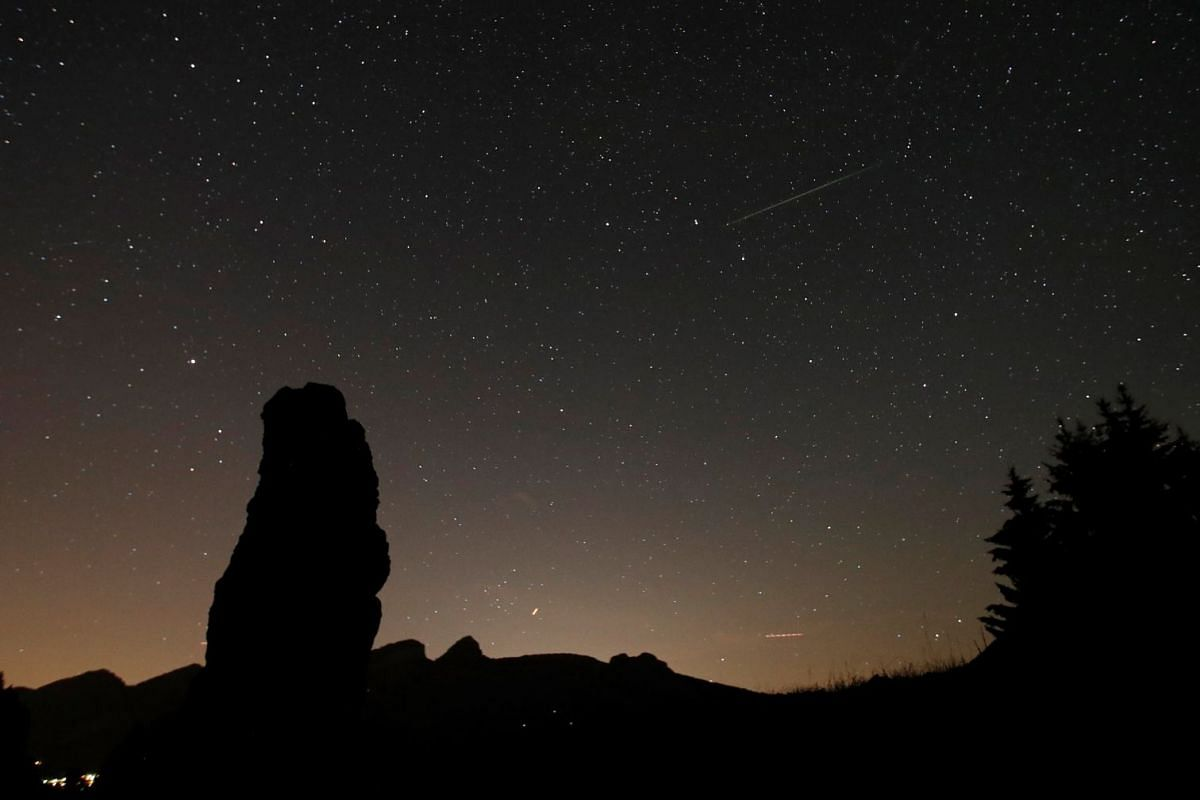 A meteor streaks past stars in the night sky next to the Cornieule of Tomeley standing stone in La Forclaz, Switzerland,  during the annual Perseid meteor shower on Aug 11, 2018.