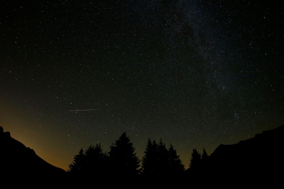 A meteor streaks past stars in the night sky in La Forclaz, Switzerland,  during the annual Perseid meteor shower on Aug 11, 2018.