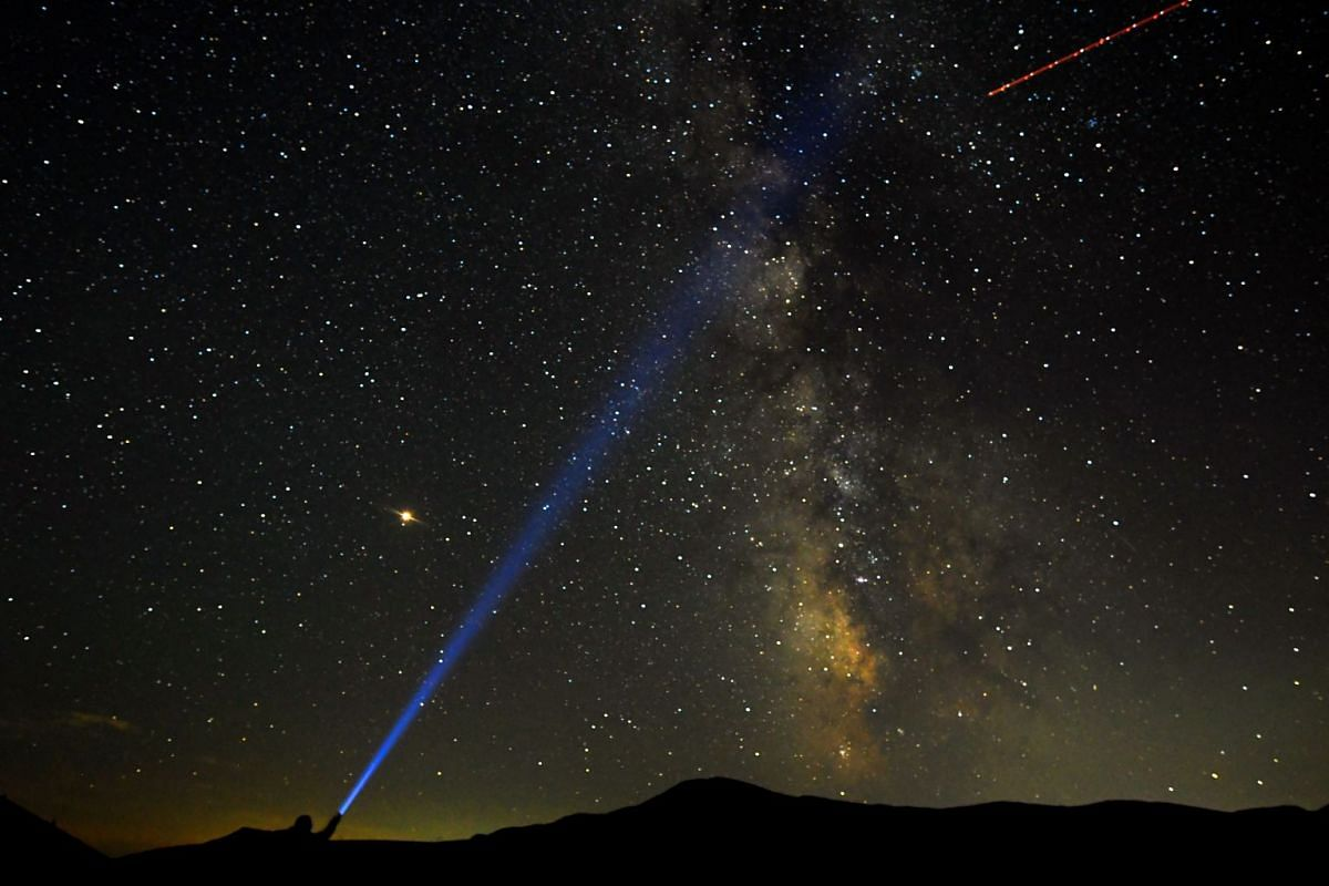 A man points his light at the Milky Way during the peak of the Perseid meteor shower at Mavrovo national park in Macedonia on Aug 12, 2018.