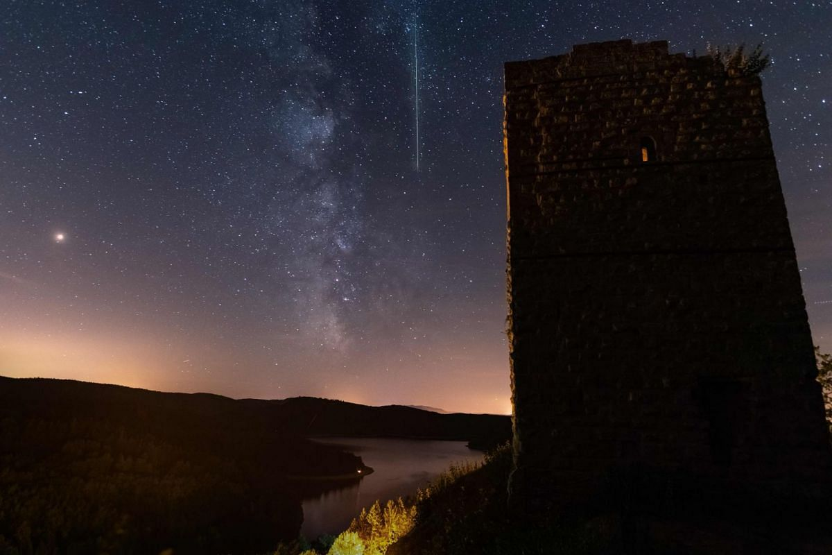 A meteor crosses the night sky during the Perseid meteor shower in Pierre-Percee lake area in eastern France on Aug 12, 2018.