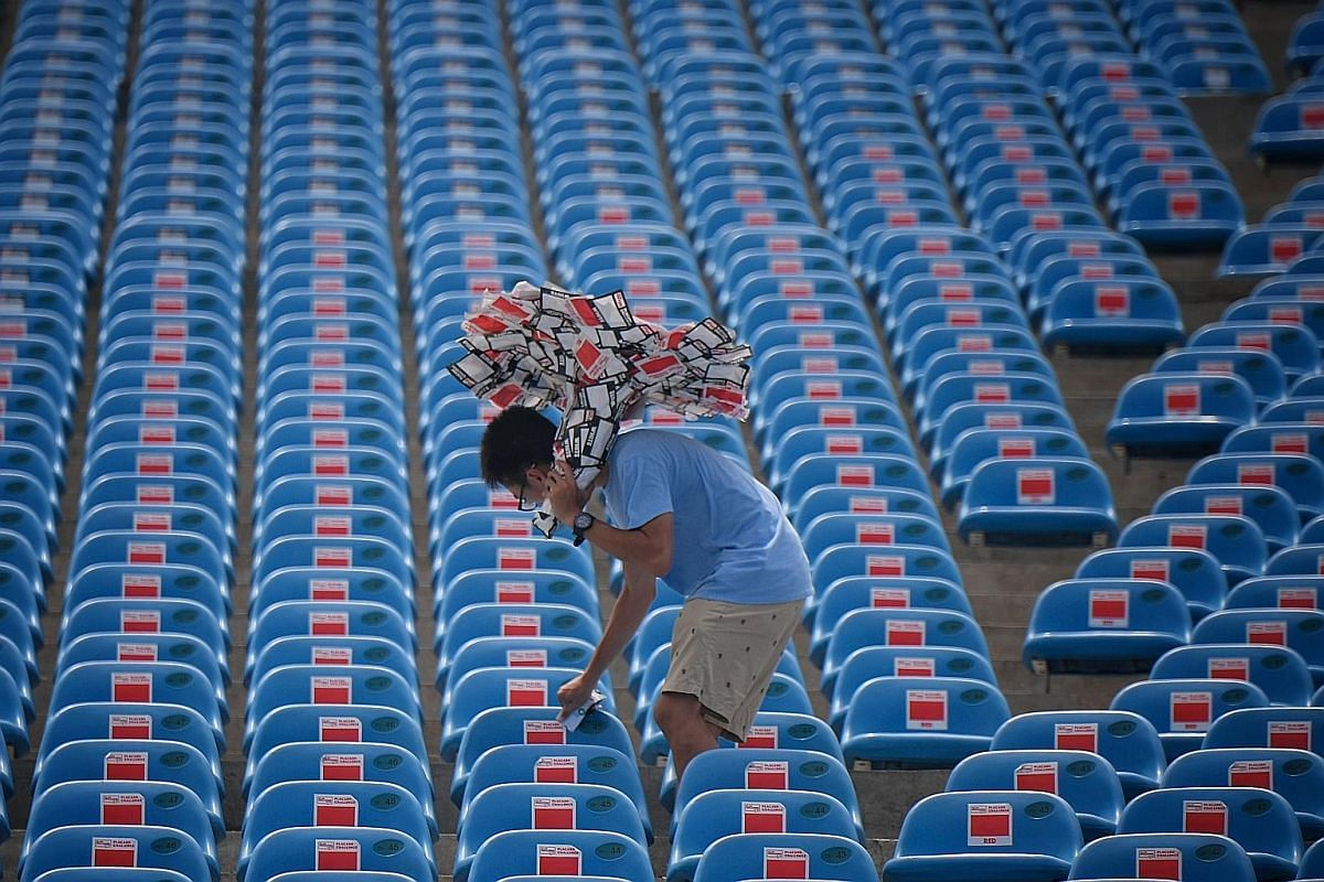"""Far left: A worker uses a stack of stickers as an """"umbrella"""" to shield himself from the afternoon heat as he goes about removing them from the seats. Left: A member of the cleaning crew, Mr Zarak Khan (in bright green top), 61, holds a trash bag open"""