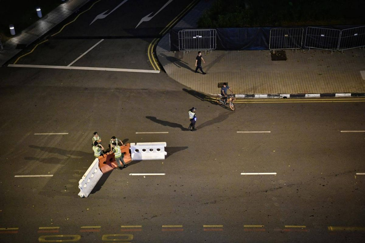 Military personnel removing barricades used during the road closures in front of the floating platform along Raffles Avenue after the national day parade.